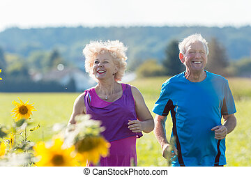 Cheerful senior couple jogging together outdoors in the countryside