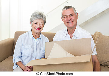 Cheerful senior couple moving into new home smiling at...
