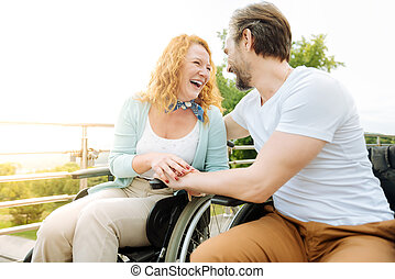 Cheerful senior couple sititng in the wheelchairs outdoors