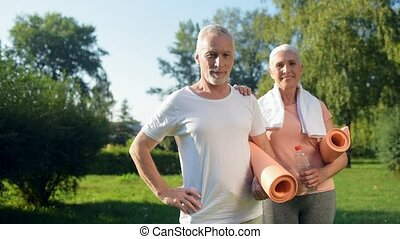 Cheerful senior couple standing in the park with the exercises mat