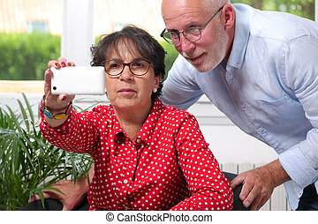 Cheerful senior couple taking selfie at home