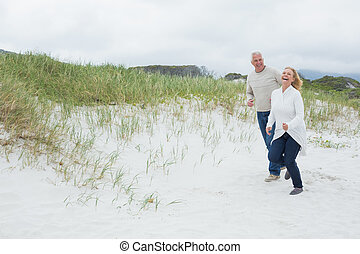 Cheerful senior couple walking at beach