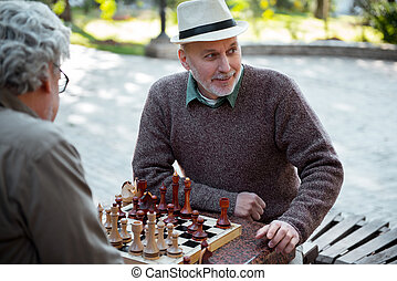Cheerful senior friends playing chess outdoor