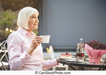 Cheerful senior lady drinking hot drink outdoors