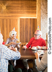 Cheerful senior lady giving cake with candle to friend