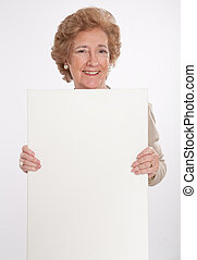 Cheerful senior lady holding a vertical blank board