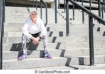 Cheerful senior lady recreating after training on stadium steps outdoor