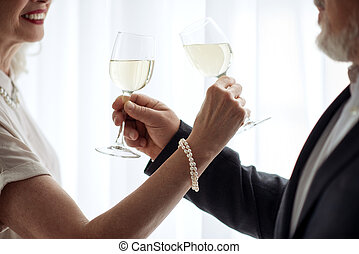 Cheerful senior loving couple drinking champagne together