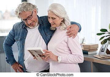 Cheerful senior man and woman watching loving photograph