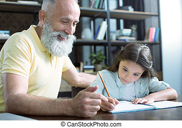 Cheerful senior man doing homework with granddaughter