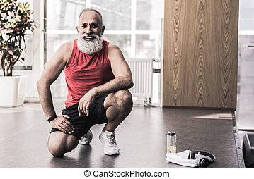 Cheerful senior man is resting after good training with smile