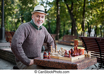 Cheerful senior man playing chess outdoor