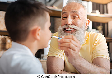 Cheerful senior man putting a paint dot on grandsons nose