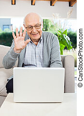 Cheerful Senior Man Video Chatting On Laptop