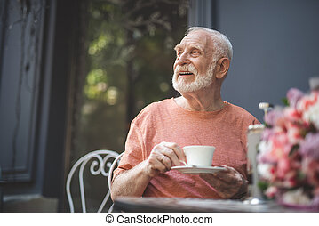 Cheerful senior man waiting for spouse in cafe