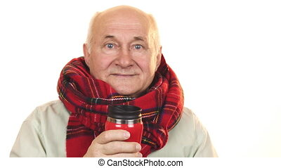 Cheerful senior man wearing a scarf holding thermos smiling happily