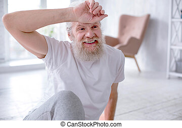 Cheerful senior man wiping off sweat after exercise