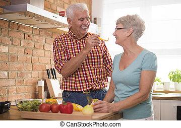 Cheerful senior marriage preparing healthy meal
