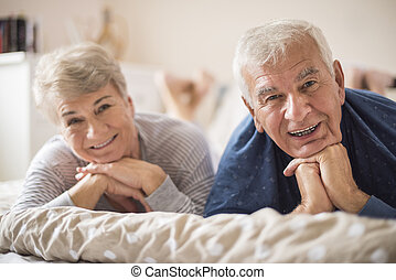Cheerful senior marriage resting in the bedroom