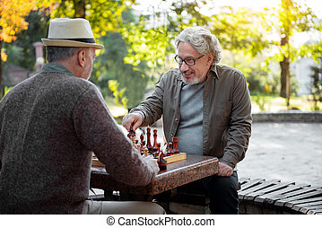 Cheerful senior men playing chess together outdoor