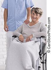 Cheerful senior on wheelchair with nurse