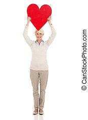 senior woman holding heart shape - cheerful senior woman...
