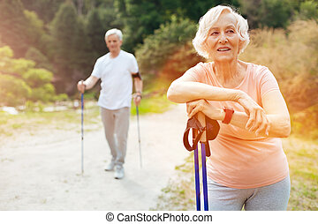 Cheerful senior woman leaning on her walking poles