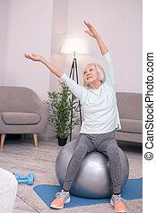Cheerful senior woman leaning sideways while sitting on yoga ball