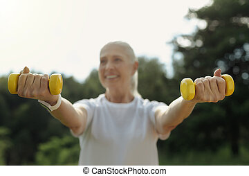 Cheerful senior woman lifting dumbbells outdoors
