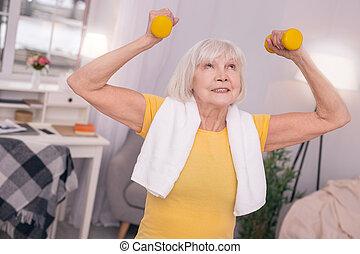 Cheerful senior woman lifting up dumbbells