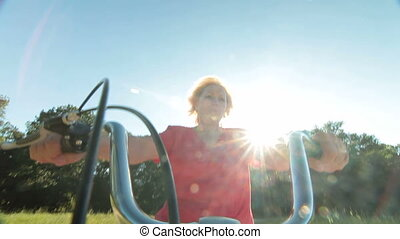 Cheerful senior woman riding bicycle against sun and blue sky POV