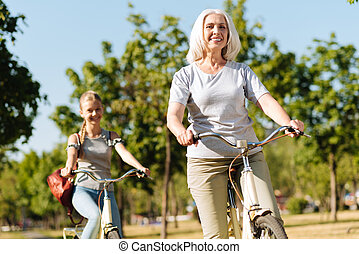 Cheerful senior woman riding bicycle with her granddaughter