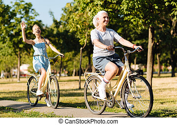 Cheerful senior woman riding bicycles with her granddaughter