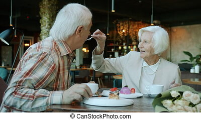 Cheerful senior woman is treating husband to delicious cake talking laughing enjoying dinner indoors in cafe. Meals and relationship concept.