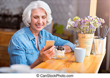 Cheerful senior woman using cell phone