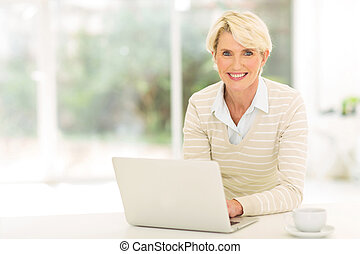 senior woman using computer - cheerful senior woman using ...