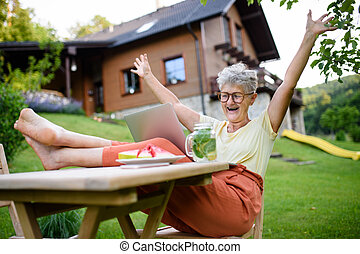 Cheerful senior woman with laptop working outdoors in garden, home office concept.