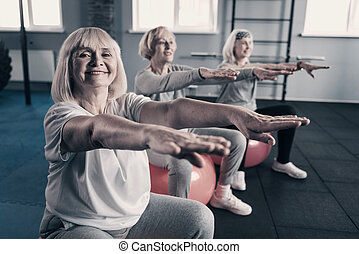 Cheerful senior women exercising on fitness balls