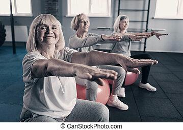 Cheerful senior women exercising on fitness balls