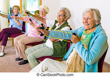 Cheerful senior women exercising their arms - Group of four...