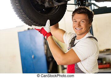 Cheerful serviceman checking suspension in a car workshop