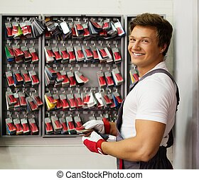 Cheerful serviceman near stand with colour samples in car body workshop