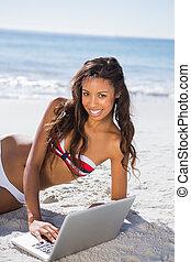 Cheerful sexy young woman in bikini using her laptop