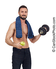 Cheerful shirtless man with apple and dumbbell