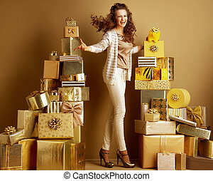 cheerful shopper woman showing yellow piggy bank with gold bow