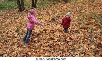 Cheerful siblings jumping in pile of autumn leaves