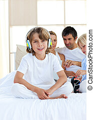 Cheerful siblings listening music with headphones