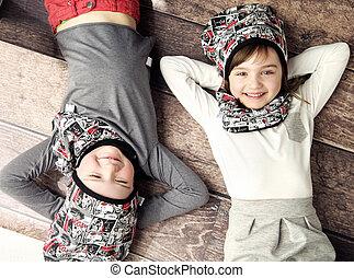 Cheerful siblings lying on the wooden floor