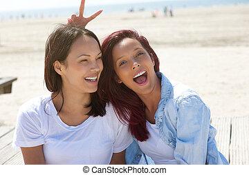 Cheerful sisters having fun at the beach