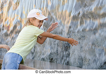 Cheerful six year old girl in summer clothes hand trying to get the water artificial waterfall